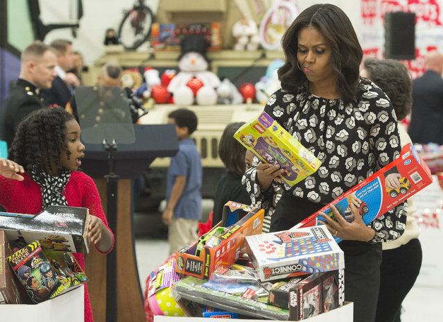 US First Lady Michelle Obama tries to decide which box to use as she sorts toys and gifts donated by the Executive Office of the President staff to the Marine Corps Reserve Toys for Tots Campaign by age at Joint Base Anacostia-Bolling in Washington, DC, December 9, 2015. (Photo by Saul Loeb/AFP Photo)