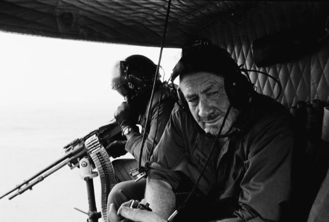 "Nobel Prize-winning author John Steinbeck wears earphones as he rides in an Army helicopter on December 17, 1966 in Vietnam over the central Vietnamese Highlands. The 64-year-old author came to Vietnam to ""go up the rivers and into the mountains"" to see it for himself. Steinbeck began his first trip to visit combat units his first field trip to visit combat units the weekend of Dec. 16, 1966. (Photo by AP Photo)"
