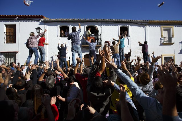 People try to catch sausages thrown from a house during the annual San Antonio Abad (Saint Anton Abbott) festival in Trigueros, southwest Spain January 25, 2015. (Photo by Marcelo del Pozo/Reuters)