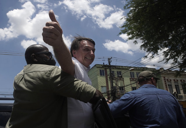 """Brazil's President Jair Bolsonaro greets supporters after voting during the run-off municipal elections in Rio de Janeiro, Brazil, Sunday, November 29, 2020. Bolsonaro, who sometimes has embraced the label """"Trump of the Tropics"""", said Sunday he'll wait a little longer before recognizing the U.S. election victory of Joe Biden, while also echoing President Donald Trump's allegations of irregularities in the U.S. vote. (Photo by Silvia Izquierdo/AP Photo)"""