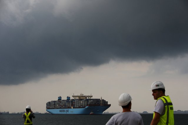 The world's largest container ship, the MV Maersk Mc-Kinney Moller, is led by pilot ships as it makes its maiden port of call at a PSA International port terminal in Singapore in this September 27, 2013 file photo. Singapore is expected to release non-oil export numbers this week. (Photo by Edgar Su/Reuters)