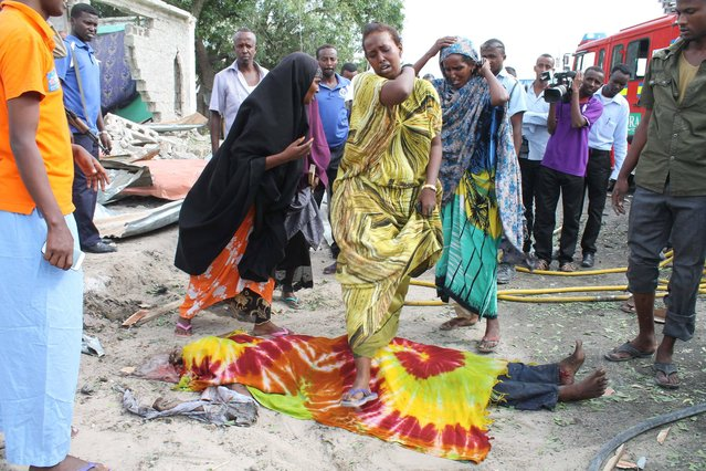A Somali lady steps over the dead body of her brother who was killed after a suicide bomber detonated his explosives near a moving convoy of African union troops, in Mogadishu, Somalia, Friday, July,12 , 2013. Police have said that at least two people were killed and seven were injured in the blast. (Photo by Farah Abdi Warsameh/AP Photo)