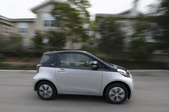 A Scion IQ electric car given to a resident of University of California, Irvine faculty housing drives down a street in Irvine, California January 26, 2015. (Photo by Lucy Nicholson/Reuters)