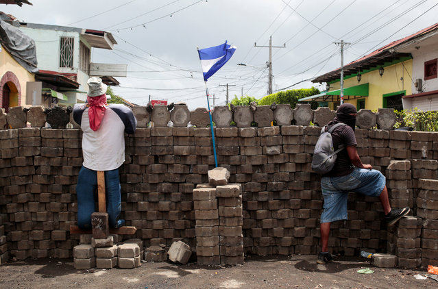 A demonstrator stands behind a barricade in the indigenous community of Monimbo in Masaya, Nicaragua July 6, 2018. (Photo by Oswaldo Rivas/Reuters)