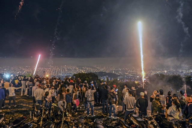 People watch fireworks during the Alborada, a tradition to celebrate the arrival of the Christmas season, in Medellin, Colombia, on December 1, 2020 amid the COVID-19 novel coronavirus pandemic. (Photo by Joaquin Sarmiento/AFP Photo)