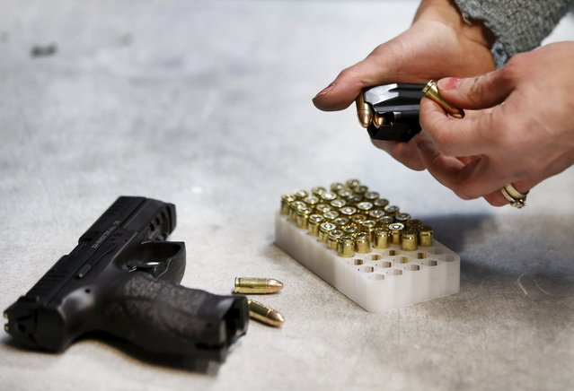 First time gun owner, Jessie Palmieri loads a bullet clip with 9mm for a H&K VP9 9mm gun at the Ringmasters of Utah gun range, in Springville, Utah on December 18, 2015. (Photo by George Frey/Reuters)