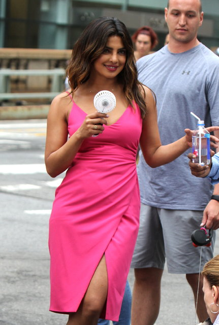 """Priyanka Chopra pictured using a fan to cool off, before taking a break from filming to walk her dog Diana at the """"Isn't it Romantic"""" movie set in Midtown, Manhattan on July 16, 2018. (Photo by Jose Perez/Splash News and Pictures)"""