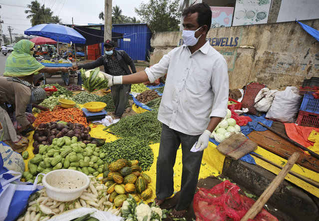 A vegetable vendor wearing gloves and face mask as a precaution against the coronavirus interacts with a customer in Bengaluru, India, Sunday, October 11, 2020. India's confirmed coronavirus toll crossed 7 million on Sunday with a number of new cases dipping in recent weeks, even as health experts warn of mask and distancing fatigue setting in. (Photo by Aijaz Rahi/AP Photo)