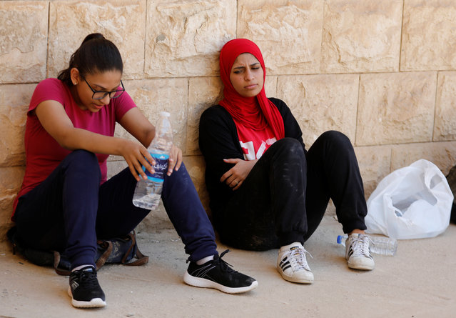 """Egyptian women from Parkour Egypt """"PKE"""" take a rest after playing around buildings on the outskirts of Cairo, Egypt on July 20, 2018. It is uncommon for women to play such sports on the streets in Egypt. A 2017 Thomson Reuters Foundation survey of experts on how women fared in mega cities rated Cairo as the world's most dangerous megacity for women, while London came out as best. (Photo by Amr Abdallah Dalsh/Reuters)"""