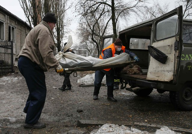 Men load the body of a victim of shelling into a vehicle at a site hit by shelling in Donetsk, eastern Ukraine, February 1, 2015. (Photo by Maxim Shemetov/Reuters)