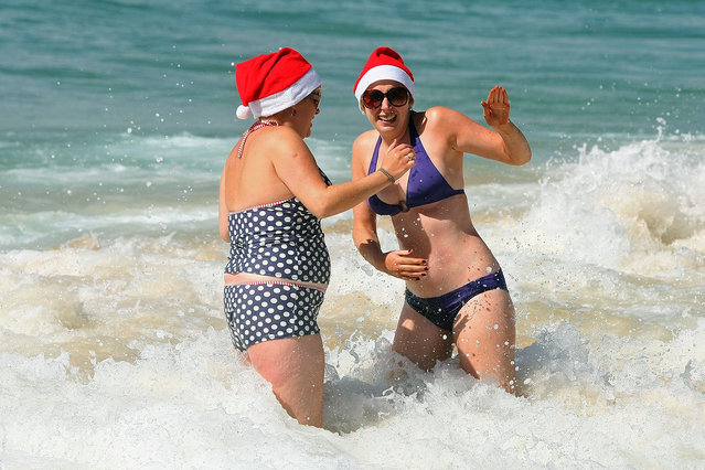 Women play in the shallow water at Bondi Beach on December 25, 2011 in Sydney, Australia. Bondi Beach is a popular place for tourist on Christmas Day. (Photo by Don Arnold/Getty Images)