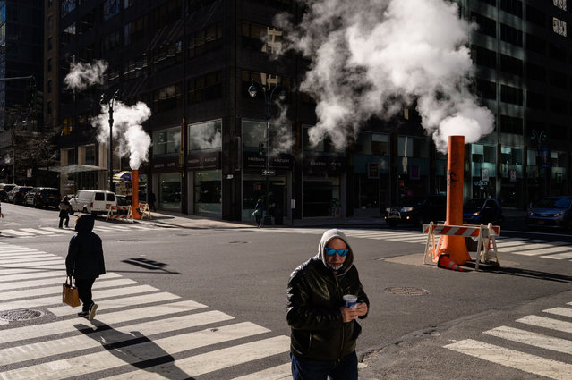Pedestrians and traffic make their way across an intersection in Manhattan, New York, on March 15, 2021. (Photo by Ed Jones/AFP Photo)