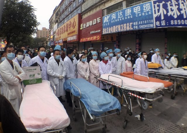 Medical personnel wait next to stretchers after a fire broke out at a wholesale market building in Huidong county, Guangdong province February 5, 2015. The fire at the warehouse in China has killed at least 17 people, state news agency Xinhua said on Friday, the latest disaster in a country with a poor record on work safety. (Photo by Reuters/Stringer)