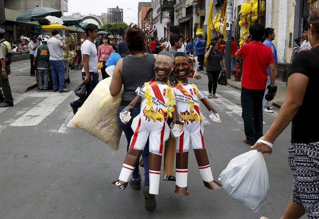 A woman carries effigies of  Peru's soccer player Jefferson Farfan in a market in Lima, Peru, December 30, 2015. (Photo by Mariana Bazo/Reuters)
