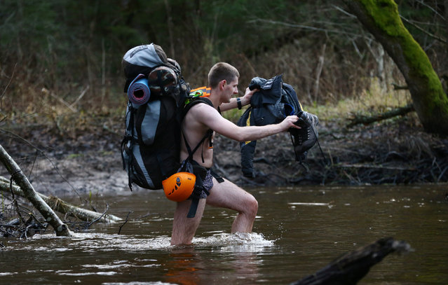 "A Belarussian tourist crosses the river as he takes part in ""Search and rescue operations – 2016"", a three-day competition, near the village of Priselki, Belarus, November 25, 2016. Photo taken November 25, 2016. (Photo by Vasily Fedosenko/Reuters)"