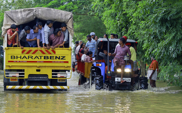 Flood affected people are rescued in a tractor, right as volunteers go for rescue work in a truck, left, at Kainakary in Alappuzha district, Kerala state, India, Friday, August 17, 2018. Rescuers used helicopters and boats on Friday to evacuate thousands of people stranded on their rooftops following unprecedented flooding in the southern Indian state of Kerala that killed more than 320 people in the past nine days, officials said. (Photo by Tibin Augustine/AP Photo)