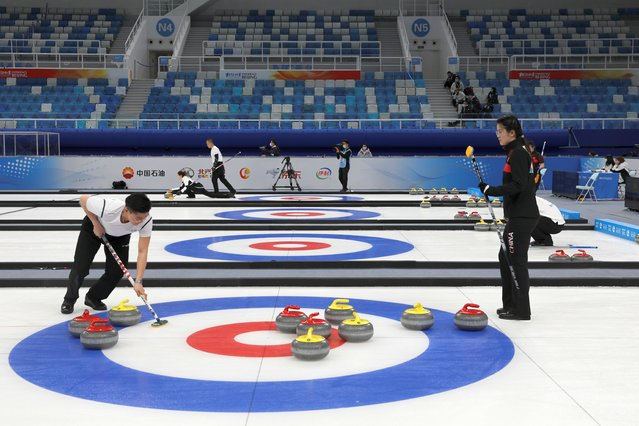 "Athletes take part in a curling competition held as a test event for the 2022 Olympic Winter Games, at the National Aquatics Center, known colloquially as the ""Ice Cube"" in Beijing, China on April 1, 2021. (Photo by Tingshu Wang/Reuters)"