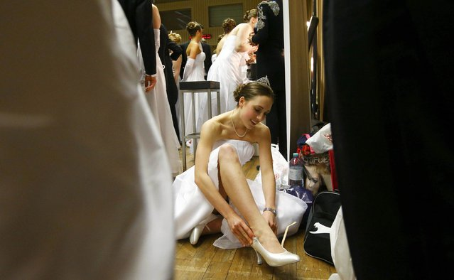 A dancer puts on her shoes before the opening ceremony of the Opera Ball in Vienna February 12, 2015. The traditional ball is opened by the Austrian president and features a musical programme with solists and artists from the Vienna Philharmonic and State Ballet before the 144 debutants and debutantes lead into the festivities with a Strauss waltz. Tickets start at 250 euros ($340) and a box costs as much as 18,500 euros ($25,000). (Photo by Leonhard Foeger/Reuters)