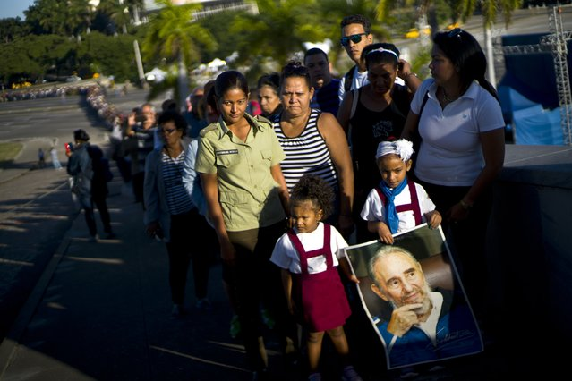 A child holds a poster of Fidel Castro as mourners wait their turn to visit the memorial site for the late leader at the Revolution Plaza in Havana, Cuba, Tuesday, November 29, 2016. (Photo by Ramon Espinosa/AP Photo)