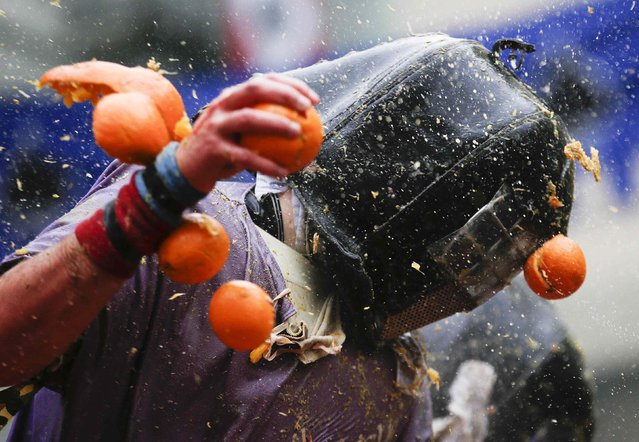 A member of a rival team is hit by an orange during an annual carnival battle in the northern Italian town of Ivrea February 15, 2015. (Photo by Max Rossi/Reuters)