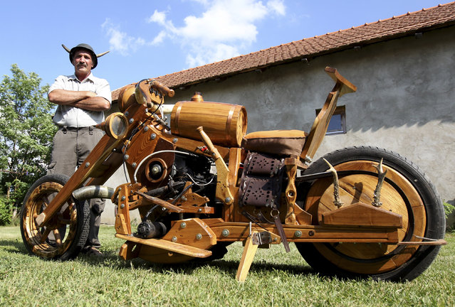 Hungarian Istvan Puskas poses with his wooden chopper in Tiszaors, 161km (100 miles) east of Budapest, June 14, 2012. Puskas, a 52-year-old tractor driver, built his bike in two years from firewood. (Photo by Laszlo Balogh/Reuters)