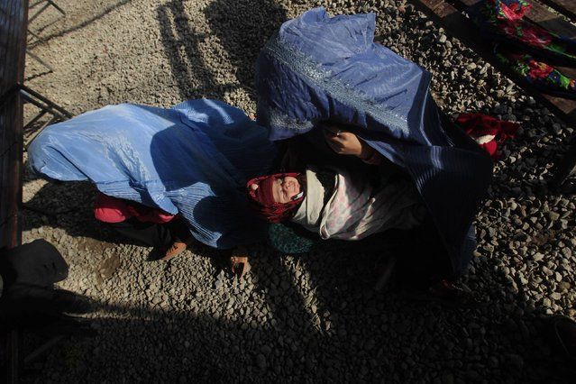 An Afghan refugee woman, clad in burqa, sits on ground with her baby while waiting to go back to Afghanistan with others, at the United Nations High Commissioner for Refugees (UNHCR) office on the outskirts of Peshawar February 13, 2015. (Photo by Fayaz Aziz/Reuters)