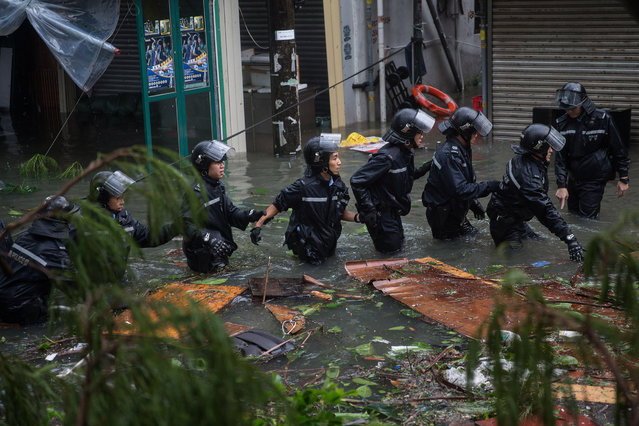 Police officers patrol a flooded street during a rescue operation due to Typhoon Mangkhut in Lei Yu Mun, Hong Kong, China, 16 September 2018. The No 10 typhoon warning was raised in the early hours as Typhoon Mangkhut  sweeps past Hong Kong. (Photo by Jerome Favre/EPA/EFE)