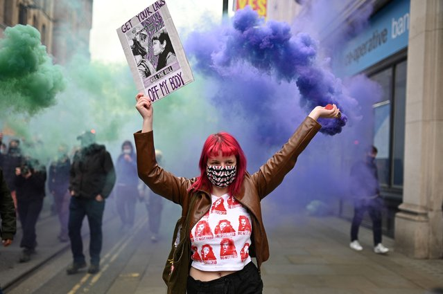 """A demonstrator holds a flare and a placard as she protests against the Police, Crime, Sentencing and Courts Bill 2021 in central Manchester on May 1, 2021. Previous """"Kill the Bill"""" demonstrations have turned violent, with protesters demanding the withdrawal of the legislation, which critics say harshly restricts the right to peaceful protest. (Photo by Oli Scarff/AFP Photo)"""