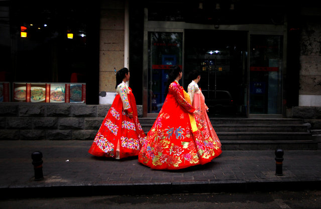 Workers from a nearby North Korean restaurant walk along a footpath wearing traditional costumes in central Beijing June 18, 2012. (Photo by David Gray/Reuters)