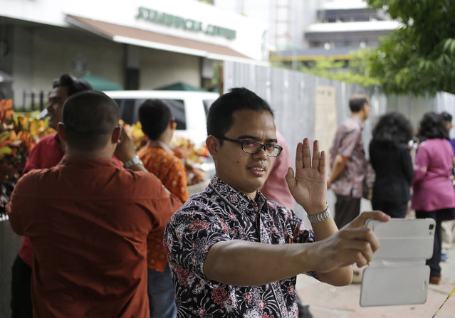 A man takes a selfie outside the Starbucks cafe where Thursday's attack occurred in Jakarta, Indonesia, on Friday, January 15, 2016. (Photo by Dita Alangkara/AP Photo)
