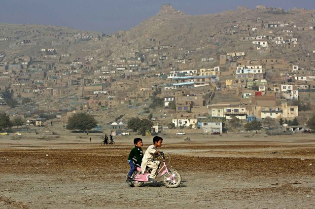 Haseebullah 7, rides his bicycle with a friend on the outskirts of Kabul, Afghanistan, Thursday, November 3, 2016. (Photo by Rahmat Gul/AP Photo)