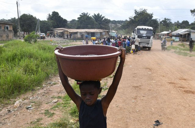 """A child carries a bucket of water after a worker of the National Office of Drinking Water (ONEP) distributed water to the population on June 2, 2018 in a district of Bouake, central Ivory Coast, where the largest dam of the """"Societe de Distribution de l'Eau de la Cote d'Ivoire"""" (SODECI – Water Distribution Company of Ivory Coast) has dried for several weeks. The dam that provides 70% of the water for the centre of the city is dry and only a few districts have water intermittently. (Photo by Issouf Sanogo/AFP Photo)"""