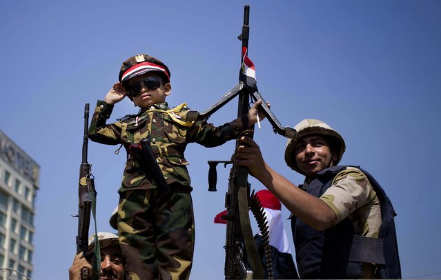 An Egyptian boy in an army costume salutes while posing next to army soldiers atop an armored vehicle guarding an entrance to Tahrir Square, on Oktober 6, 2013. (Photo by Hassan Ammar/Associated Press)