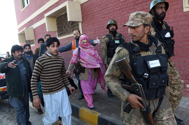 Pakistani army soldiers rescue people from Bacha Khan university following an attack by militants in Charsadda, about 50 kilometres from Peshawar, on January 20, 2016. At least 21 people died in an armed assault on a university in Pakistan on January 20, where witnesses reported two large explosions as security forces moved in under dense fog to halt the bloodshed. (Photo by A. Majeed/AFP Photo)