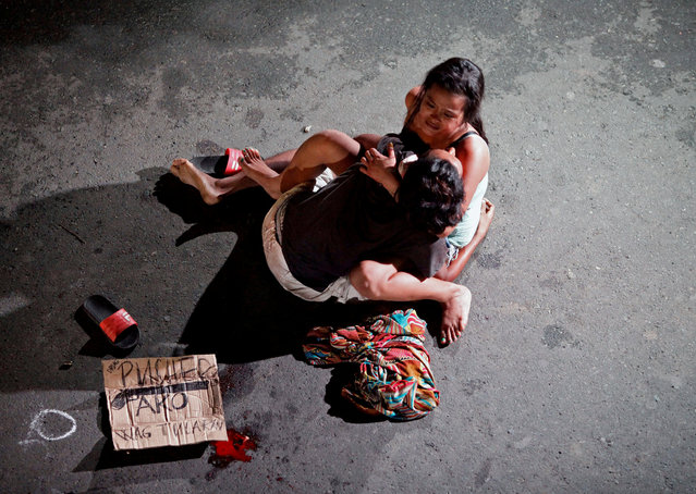 Jennilyn Olayres, 26, weeps over the body of her partner, who was killed on a street in Pasay city, Metro Manila, Philippines July 23, 2016. (Photo by Czar Dancel/Reuters)