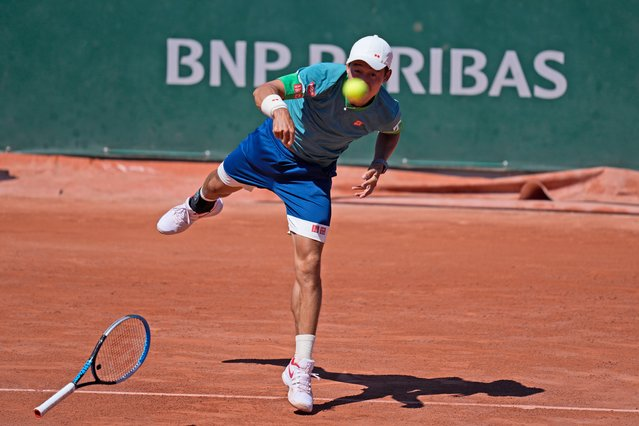 Japan's Kei Nishikori loses his racket as he serves the ball to Italy's Alessandro Giannessi during their first round match of the French Open tennis tournament at the Roland Garros stadium Sunday, May 30, 2021 in Paris. (Photo by Thibault Camus/AP Photo)
