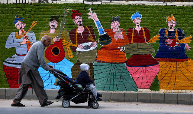 In this Janusry 2, 2018, file photo, a man pushes his grandchild in a stroller while passing a mural painted on the boundary wall of a school in Islamabad, Pakistan. Pakistan says it will seek a bailout loan from the International Monetary Fund to address a mounting balance of payments crisis, Finance Minister Asad Umar said Monday. (Photo by Anjum Naveed/AP Photo)