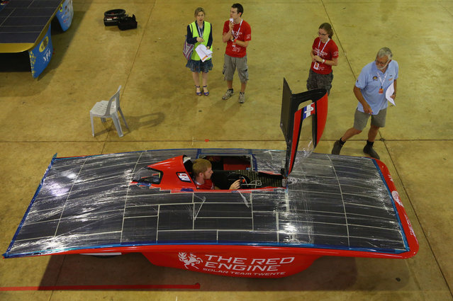 A driver sits  inside of The RED Engine from the Solar Team Twente, University of Twente and Saxion in the Netherlands as the solar car is examined as cars are presented to the scrutineers for inspection and confirmation of their regulatory compliance and structural integrity on October 2, 2013 in Darwin, Australia. (Photo by Scott Barbour/Getty Images for the World Solar Challenge)