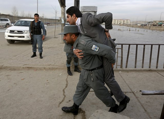 An Afghan policeman carries a wounded man at the site of a suicide attack in Kabul March 25, 2015. Six people were killed and more than 30 injured in the suicide bombing in the Afghan capital on Wednesday that struck close to the presidential palace in the heart of the city, the Interior Ministry said. The suicide bomber had been travelling in a vehicle packed with explosives and it was not immediately clear what the target of the attack had been. (Photo by Omar Sobhani/Reuters)