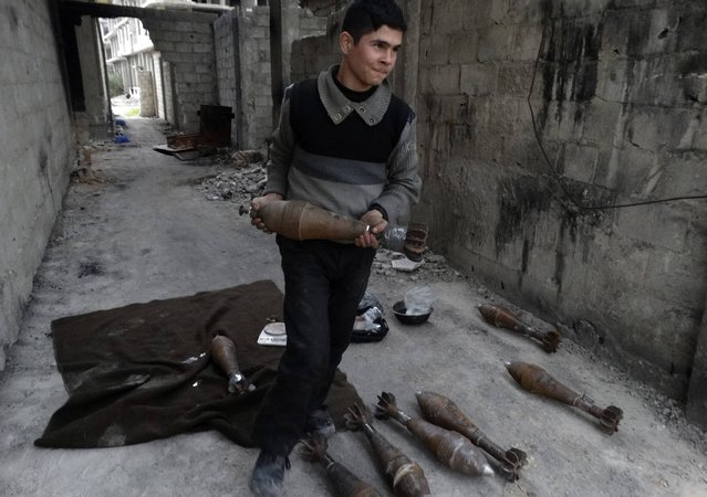 A Free Syrian Army fighter carries a mortar shell in Ain Tarma, in Eastern Ghouta, a suburb of Damascus January 3, 2015. (Photo by Msallam Abd Albaset/Reuters)