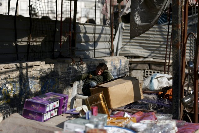 A boy rests while selling goods on a street in Douma, Syria February 3, 2016. (Photo by Bassam Khabieh/Reuters)