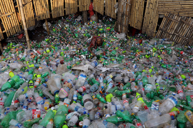 A woman works in a plastic bottle recycling factory in Dhaka, Bangladesh, October 21, 2018. (Photo by Mohammad Ponir Hossain/Reuters)