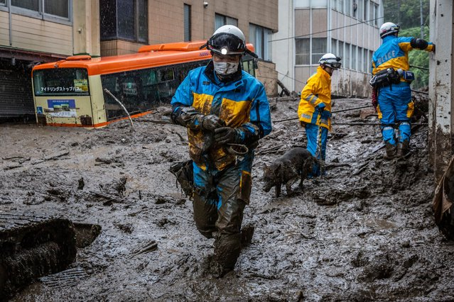A police officer with a search and rescue dog, searches the area around the site of a landslide on July 04, 2021 in Atami, Shizuoka, Japan. Torrential rain triggered a landslide, where two people are now confirmed to have been killed, with about twenty still missing. (Photo by Yuichi Yamazaki/Getty Images)