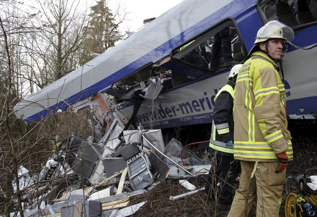Rescuers stand in front of a carriage at the site of the two crashed trains near Bad Aibling in southwestern Germany, February 9, 2016. (Photo by Josef Reisner/Reuters)