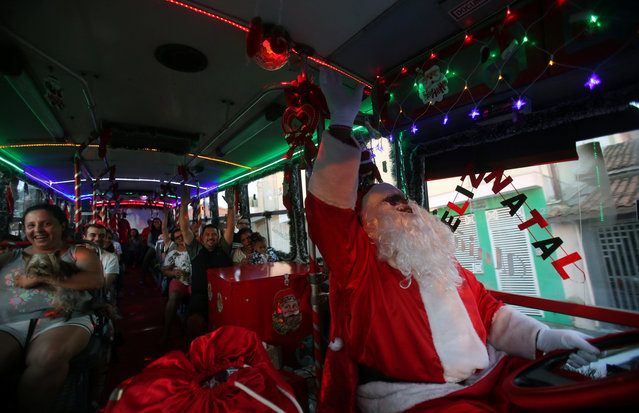 """Driver and councilman Edilson Santos, 50, who is known as """"Fumassa"""", wears a Santa Claus costume as he drives a bus decorated with Christmas ornaments in Santo Andre, Brazil December 9, 2018. (Photo by Amanda Perobelli/Reuters)"""