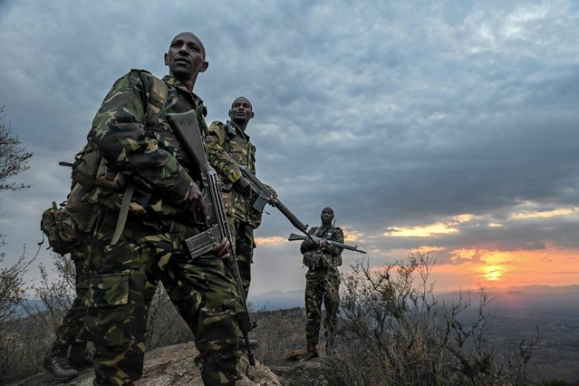 Armed officers of Lewa Wildlife Conservancy's (LWC) anti-poaching unit look out from a ridge at dawn in Meru, on July 31, 2021, as they wind up their nightly security patrol against poaching and illegal incursions into the conservancy. Despite the global condemnation of poaching and the resources that have been mobilised to safeguard endangered wildlife, well-funded and well-equipped poaching groups continue to pose a real threat to Africa's wildlife. (Photo by Tony Karumba/AFP Photo)