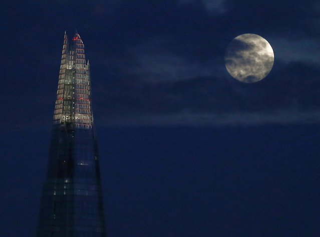 The full moon rises behind the Shard building in London December 5, 2014. (Photo by Andrew Winning/Reuters)