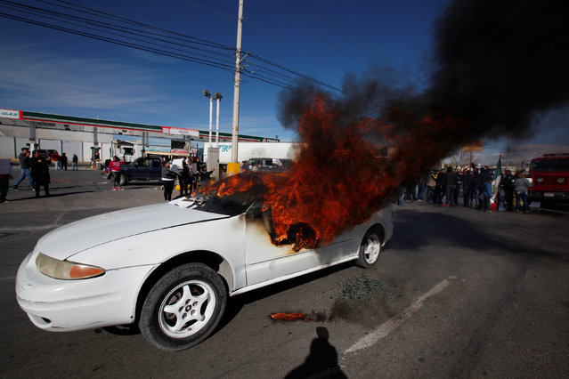 A car set ablaze by demonstrators is seen outside a petrol station during a protest against a fuel price hike in Ciudad Juarez, Mexico January 20, 2017. (Photo by Jose Luis Gonzalez/Reuters)