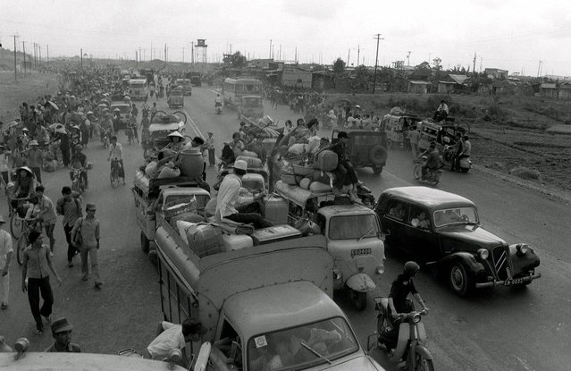 Refugees fleeing advancing communist forces flood into Saigon April 28, 1975, arriving in jammed vehicles and on foot from rural districts north of the South Vietnamese capital. The communists entered the city two days later. (Photo by H. Hung/AP Photo)