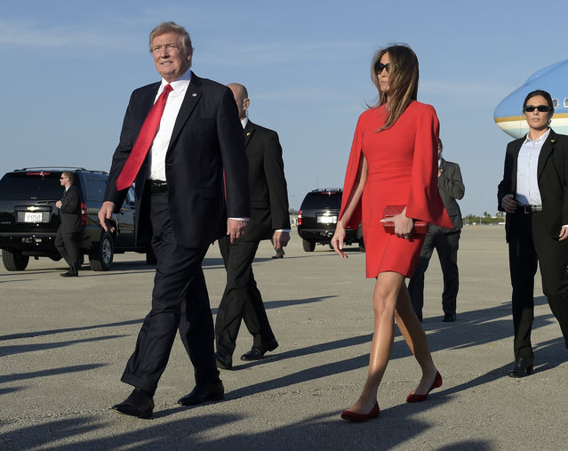 President Donald Trump walks with first lady Melania Trump after she greeted him on the tarmac after he arrived via Air Force One at Palm Beach International Airport in West Palm Beach, Fla., Friday, February 3, 2017. Trump is spending the weekend at Mar-a-Lago. (Photo by Susan Walsh/AP Photo)